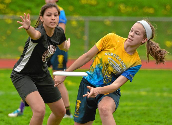 Claire Babbott-Bryan, right, of Northampton, passes against Amherst #11, Thursday in Northampton.
