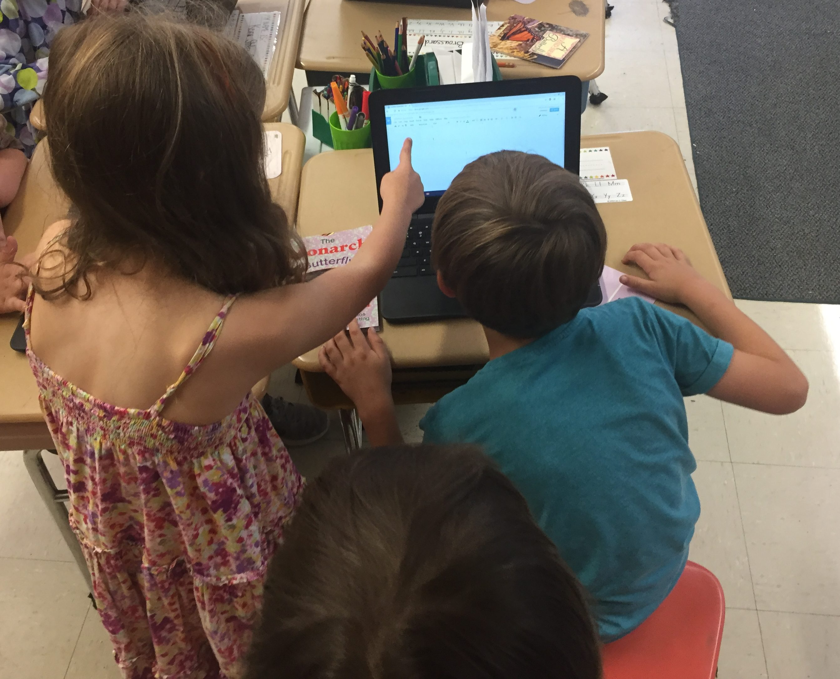 A standing student in a dress points to a chromebook screen to help out a student in a blue shirt sitting at desk.