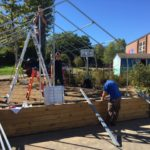 three people working on metal frame of greenhouse with one person on a ladder
