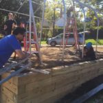 three people working to put up metal frame of greenhouse