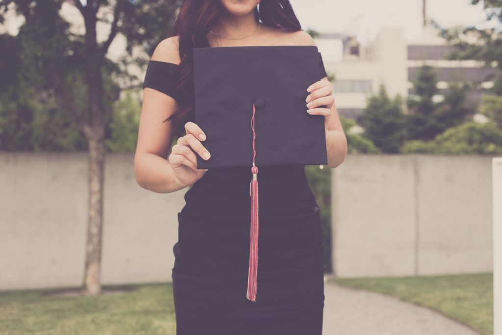 Woman standing with graduation cap.