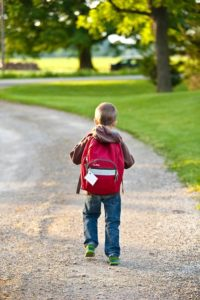 Student walking with backpack to school.