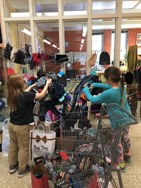 students remove donations of clothing from a a small tree in the front hall of Jackson Street school