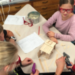 photo of students gluing prototype with Popsicle sticks.