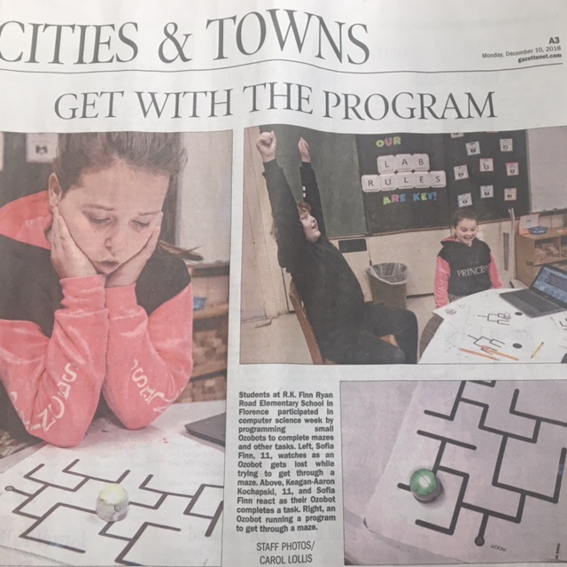 Photo of newspaper article with a student looking at robot.
