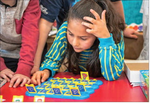 Girl with elbow on table and hand on head puzzling through the game of Guess Who.