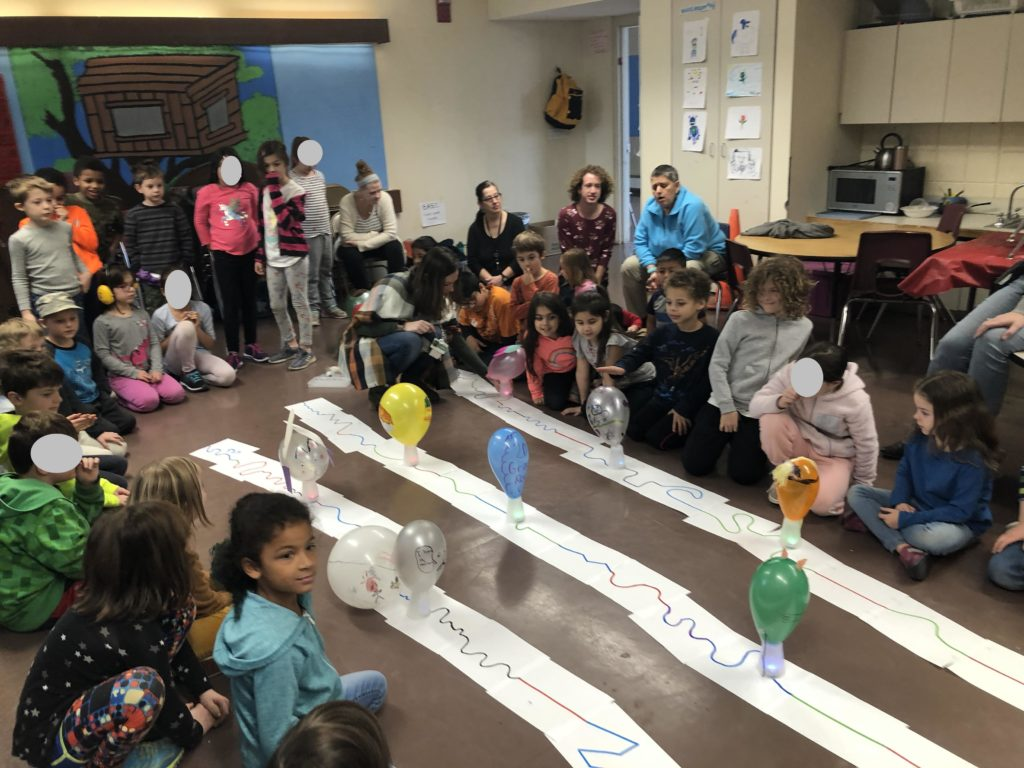 Students sit in a room watching small robots carry decorated plastic cups in a parade format.