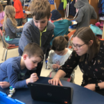 students and teacher with chromebook