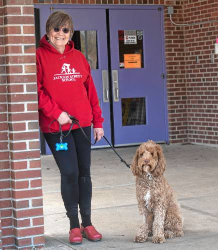 Gwen Agna with Jackson the dog standing in front of the Jackson Street School main entrance.