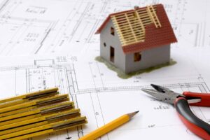 Pencils, sketches, pliers and a tiny house model